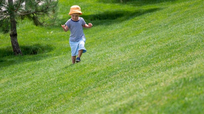 Lite kör pojken upp på den gröna kullen arkivbilder