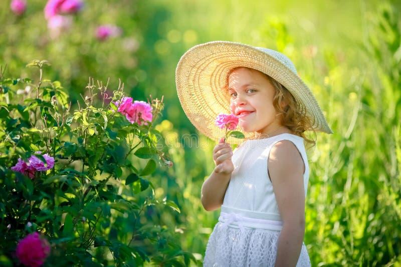 Lite kl?nning f?r blomma f?r flicka b?rande gul med den vita hatten och st?llning i det gula blommaf?ltet av Sunn hampaCrotalaria arkivfoton