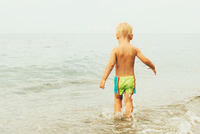 Lite kommer pojken i simningstammar in i havet, sikten från baksidan Sommarbegrepp av semestern och harmlöshet royaltyfria foton