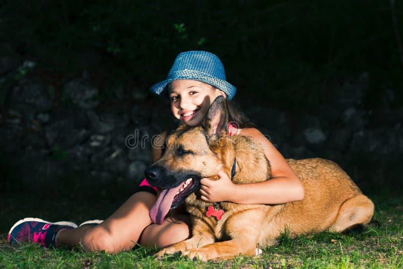 Lite kramar flickan hennes hund för den tyska herden arkivbilder