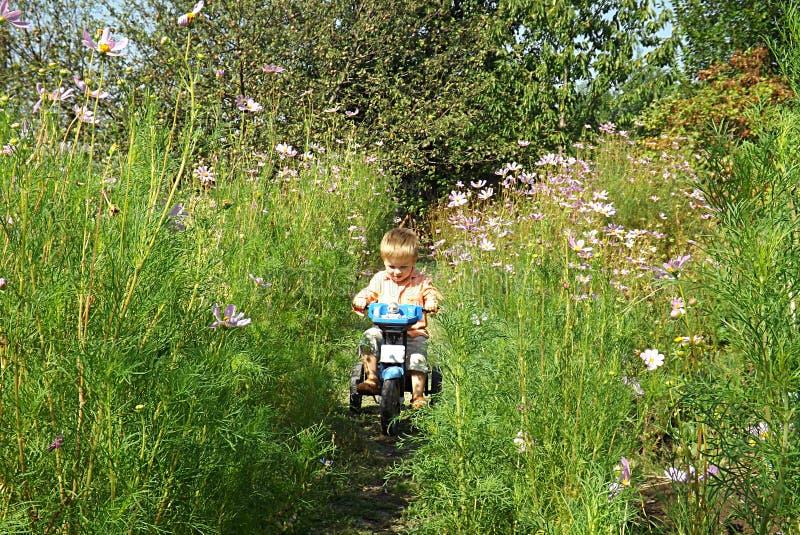 Lite lär pojken att rida en cykel arkivbild