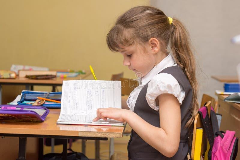 Lite läser flickan i grupp försiktigt ett dagboktillträde royaltyfri bild