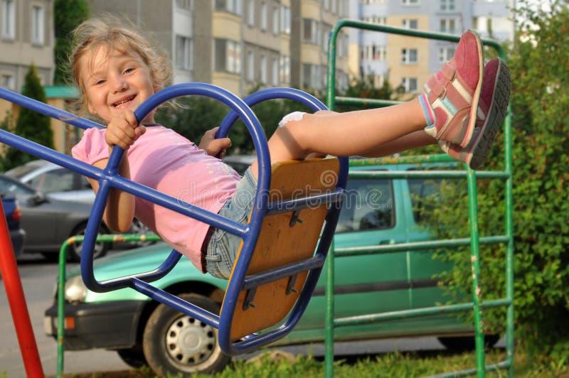Lite le flickan som tycker om att svänga i en lekplats av lägenhethus en gård för domstol fotografering för bildbyråer