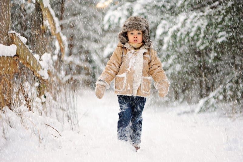 Lite ledsen pojke, i att snöa vinter royaltyfria foton