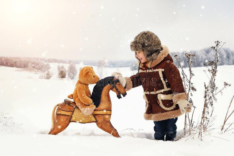 Lite lycklig pojke, i att snöa vinter arkivfoto