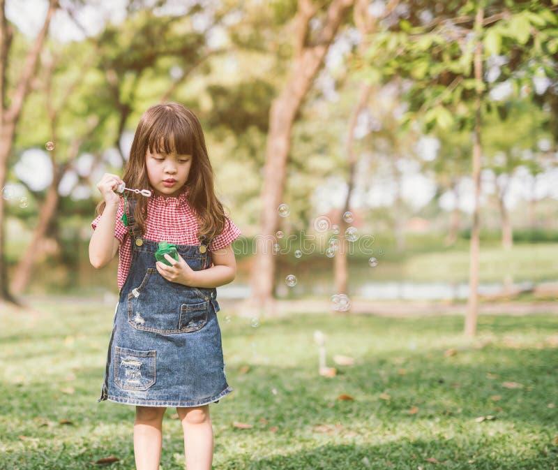Lite parkerar flickan som blåser såpbubblor i sommar arkivfoton