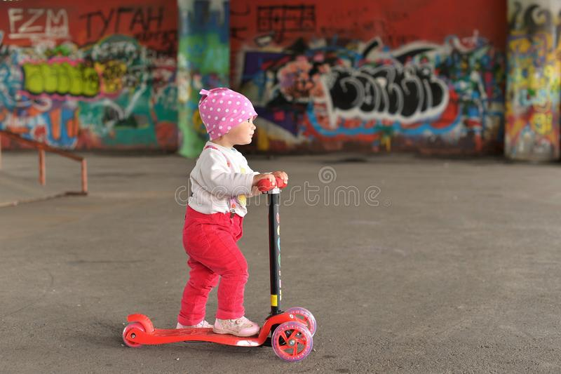 Lite parkerar flickan som rider en sparkcykel för barn` s i en skridsko royaltyfri fotografi