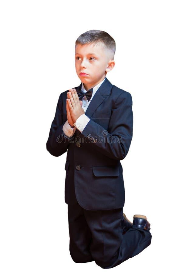 Lite pojke i en dräkt som ber som isolerar på en vit bakgrund royaltyfri foto