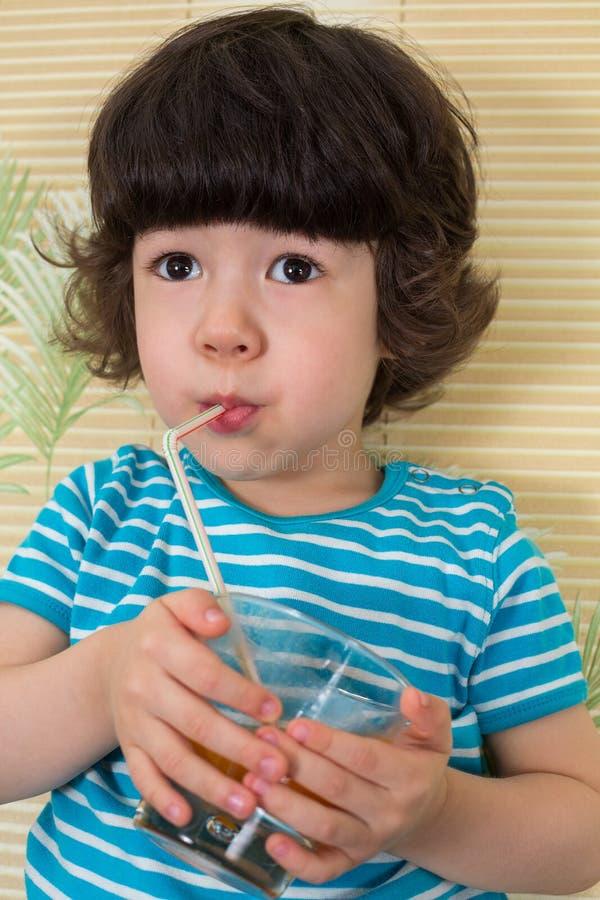 Lite pojke i en randig t-skjorta drink arkivbilder