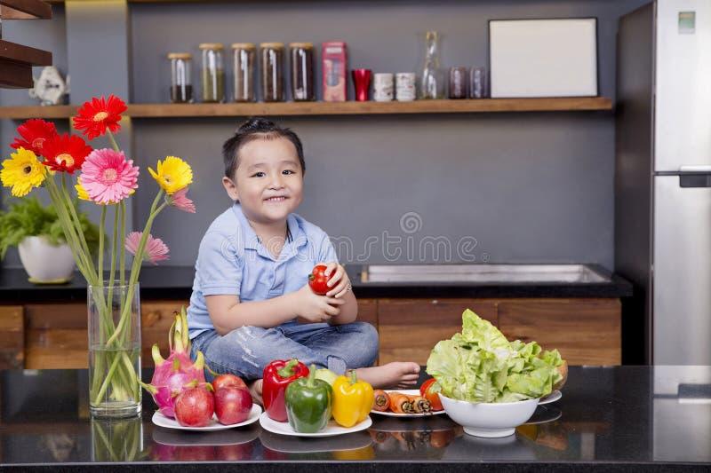 Lite pojke i köket med mycket frukt och grönsak arkivbilder
