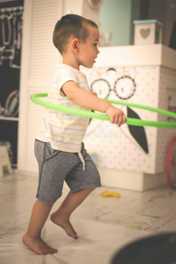 Lite pojke i lekrummet Pojken spelar med en hoolahop arkivfoto