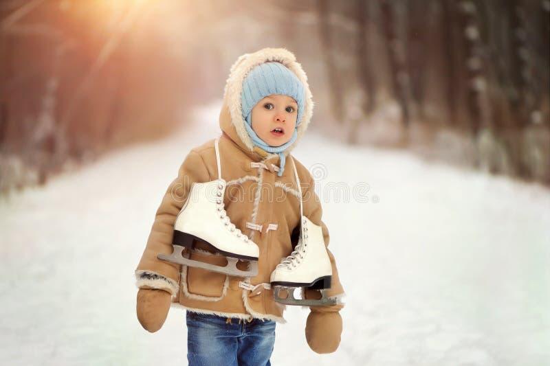 Lite pojke i päls som spelar i vintern utanför Snöig skog arkivbild