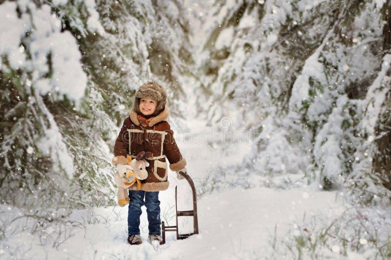 Lite pojke i päls som spelar i vintern utanför Snöig skog royaltyfria foton