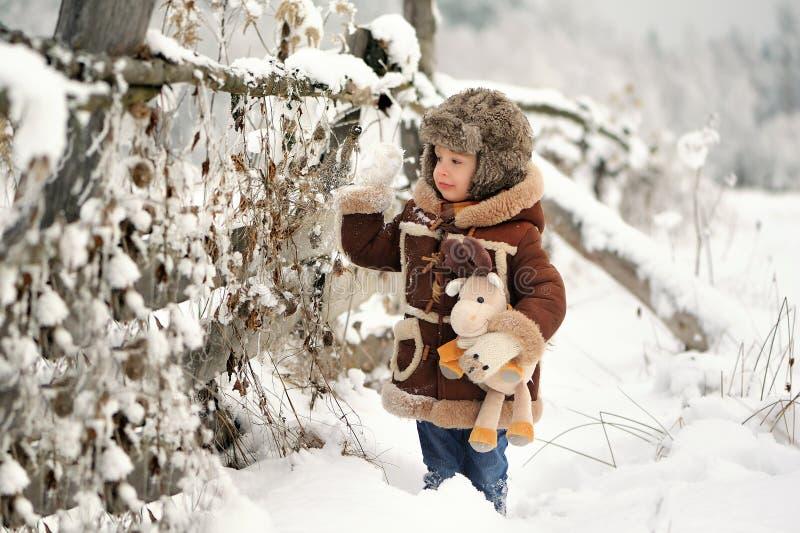 Lite pojke i päls som spelar i vintern utanför Snöig skog arkivbilder