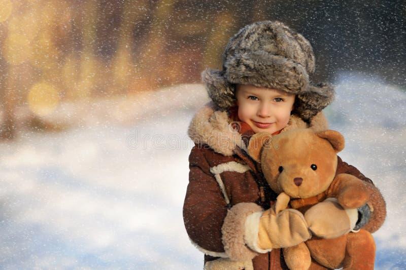 Lite pojke i päls som spelar i vintern utanför Snöig skog fotografering för bildbyråer