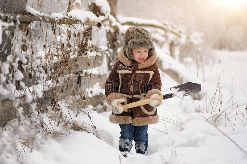 Lite pojke i päls som spelar i vintern utanför Snöig skog royaltyfria bilder