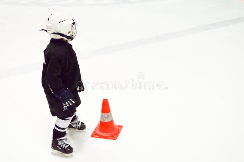 Lite pojke i svart hockeylikformig och en vit hjälm på skridskor bredvid en orange kotte på vit is på ishockeyn royaltyfria foton
