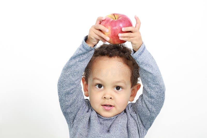 Lite pojke med äpplet överst av hans huvud fotografering för bildbyråer