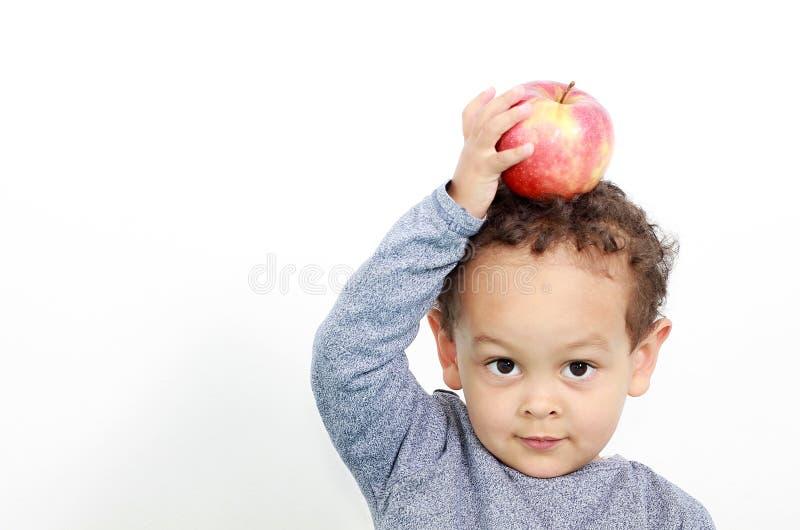 Lite pojke med äpplet överst av hans huvud royaltyfri foto