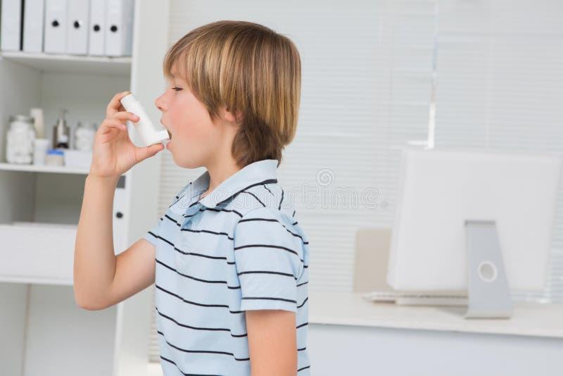 Lite pojke som använder inhalatorn royaltyfri fotografi