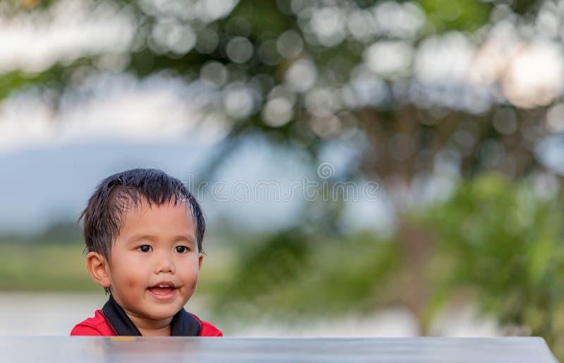 Lite pojke som kopplar av i trädgården royaltyfri foto