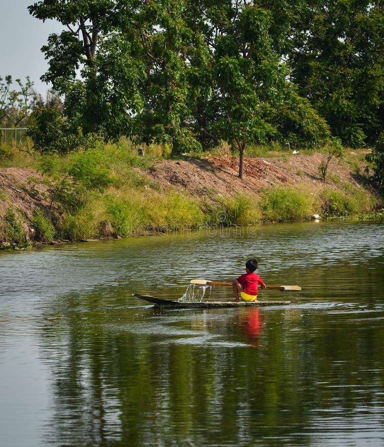 Lite pojke som ror träfartyget på kanalen arkivfoto