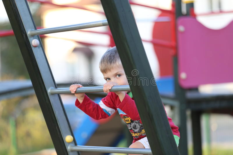 Lite pojke som spelar på en lekplats arkivbild