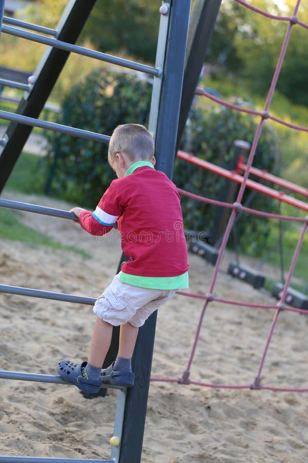 Lite pojke som spelar på en lekplats royaltyfria foton