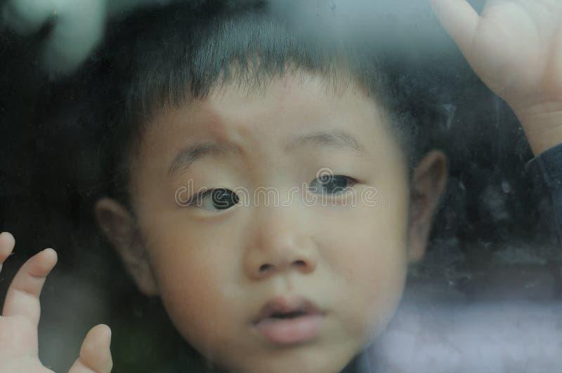 Lite pojke som ut ser fönstret royaltyfria foton