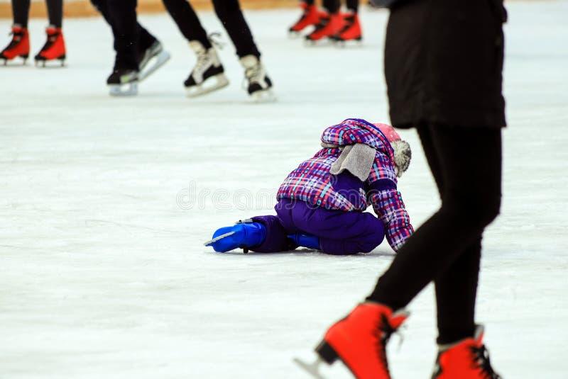 Lite pojkeskridskor och nedgångar på isen i den aktiva barn för skridskoisbana och familjsporten, vinterferier Skolasportklubbor fotografering för bildbyråer