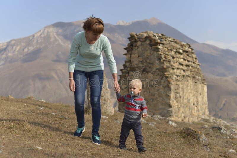 Lite reser pojken med en fredsmäklare med hans moder som går bland de forntida Ossetian byggnaderna arkivfoto