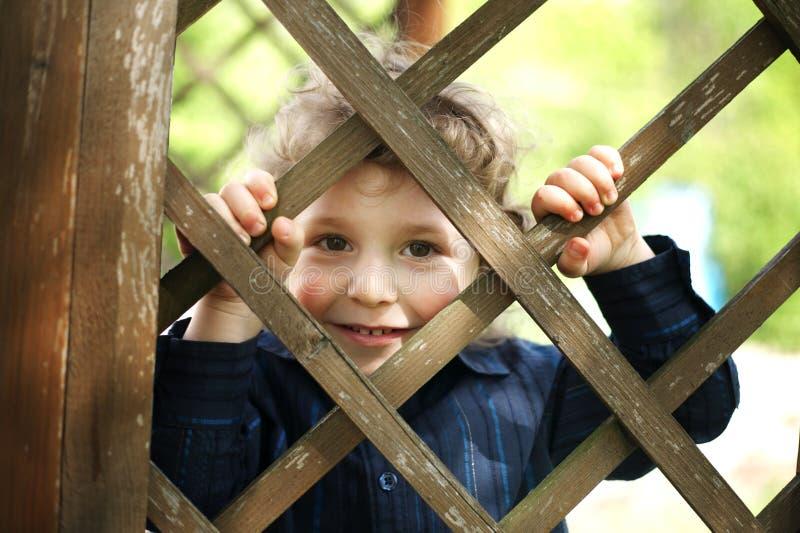 Lite rolig pojke bak staket arkivfoton