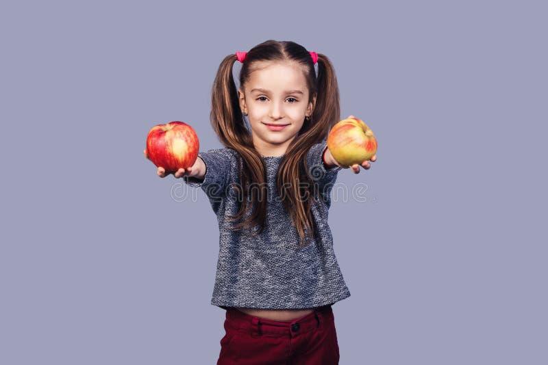 Lite rymmer erbjuder den gulliga flickan två äpplen i hennes händer och dem till dig arkivbilder