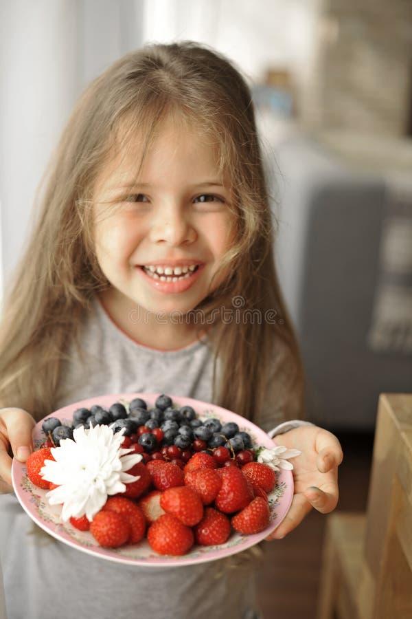 Lite rymmer flickan en platta med frukostbär, solljus från fönstret, och ett lyckligt behandla som ett barn arkivbilder