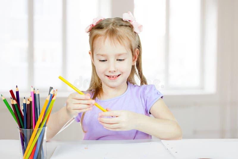 Lite rymmer ler flickan en blyertspenna och royaltyfria bilder