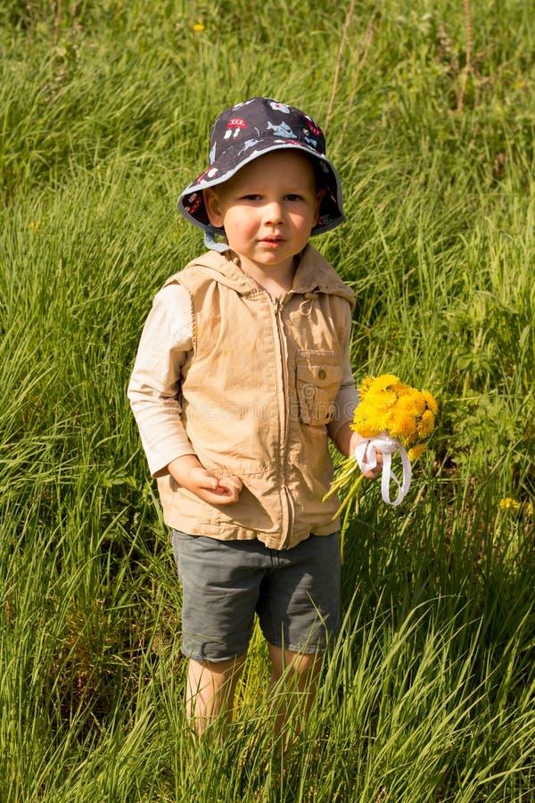 Lite rymmer pojken en stor bukett av gula maskrosor, blygt som grimacing, en gåva till hans moder royaltyfri bild