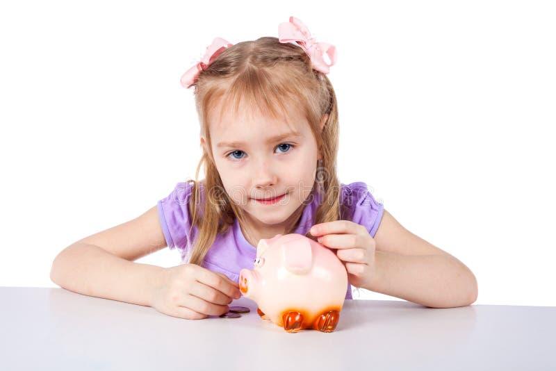 Lite sätter flickan mynt in i en svinspargris royaltyfria bilder
