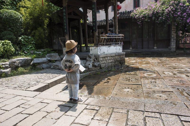Lite ser flickaanseendet bredvid en scenisk springbrunn från sidan royaltyfri fotografi