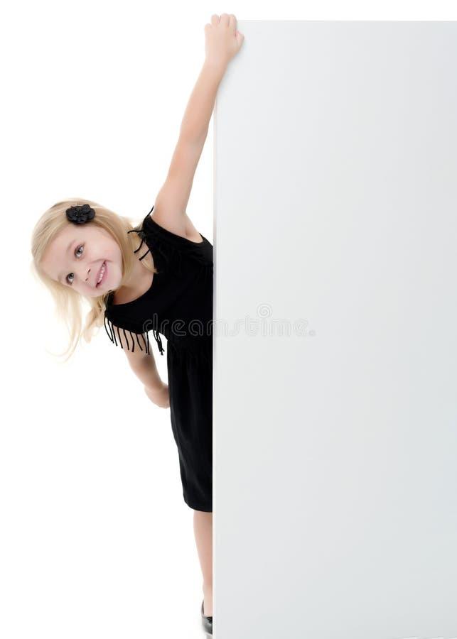 Lite ser flickan bakifrån ett tomt baner royaltyfri foto