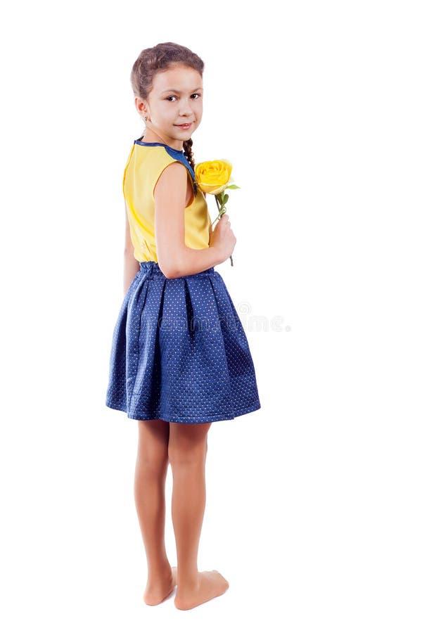 Lite ser flickan i en gul blus med en gul blomma över arkivfoton