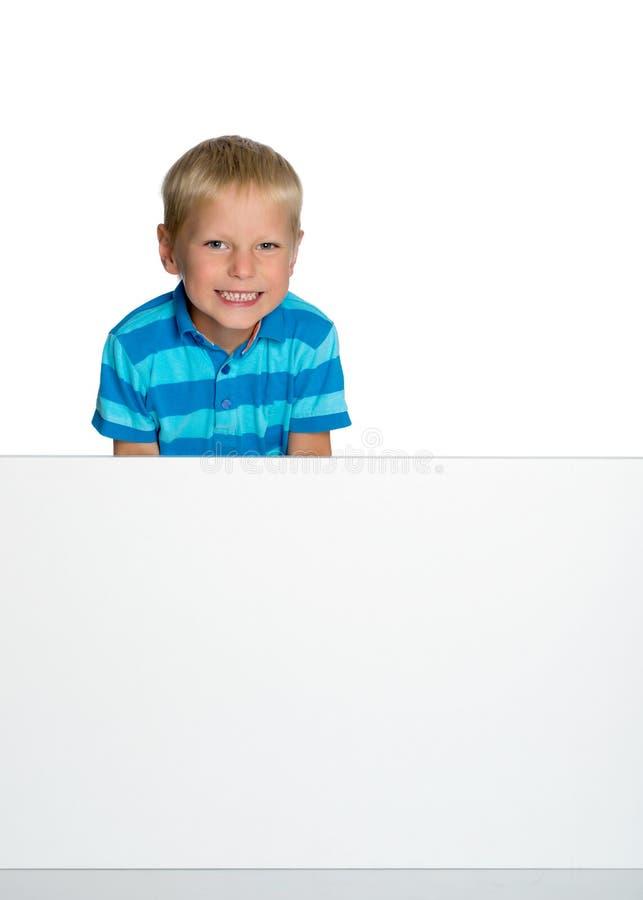 Lite ser pojken bakifrån ett tomt baner arkivfoto