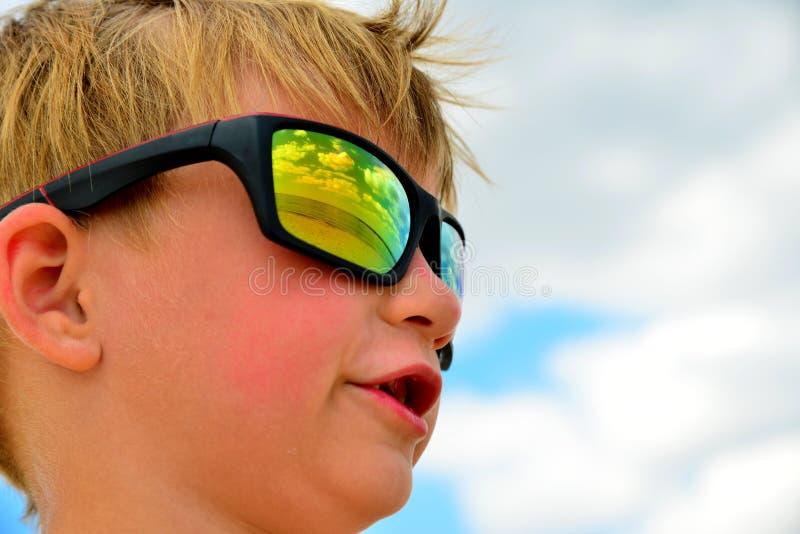 Lite ser pojken den molniga himlen med exponeringsglas Molnen reflekteras i exponeringsglaset Gula exponeringsglas mot den blåa h royaltyfri foto