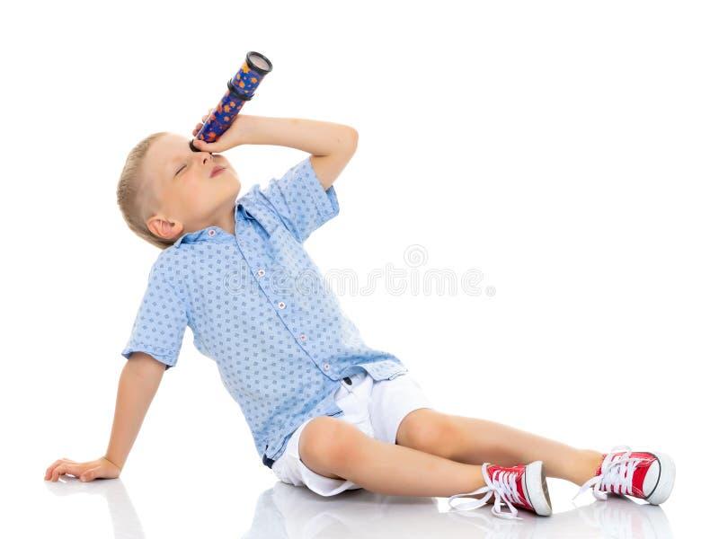 Lite ser pojken till och med ett teleskop eller en kalejdoskop royaltyfria bilder