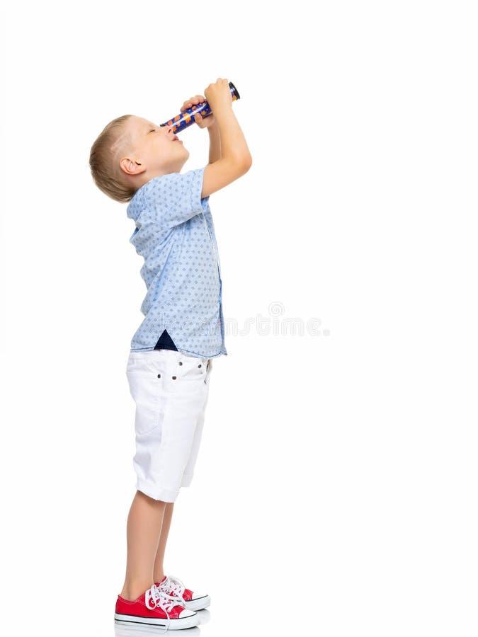Lite ser pojken till och med ett teleskop eller en kalejdoskop arkivfoton