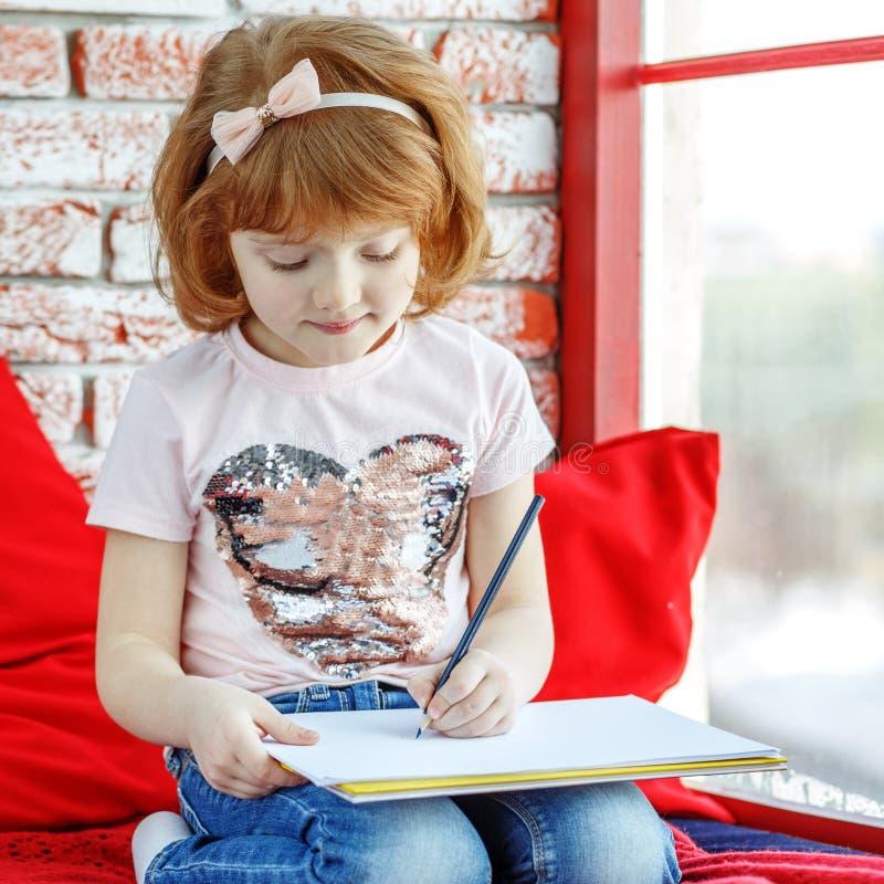 Lite sitter förskolebarnet på fönsterbrädan och dra för fönster arkivfoton