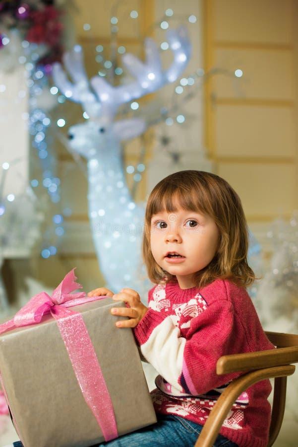 Lite sitter flickan med en gåva i hennes händer i en släde på bakgrunden av en hjort arkivbilder