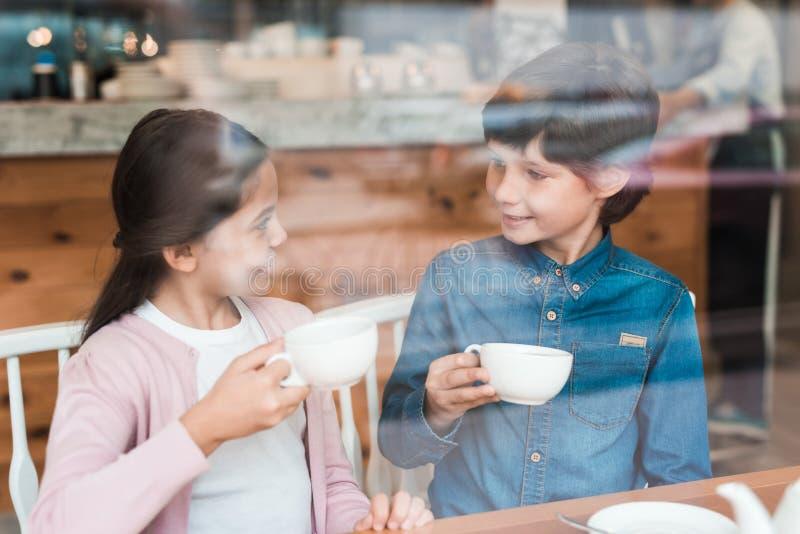 Lite sitter pojken med lite flickan i ett kafé royaltyfri foto
