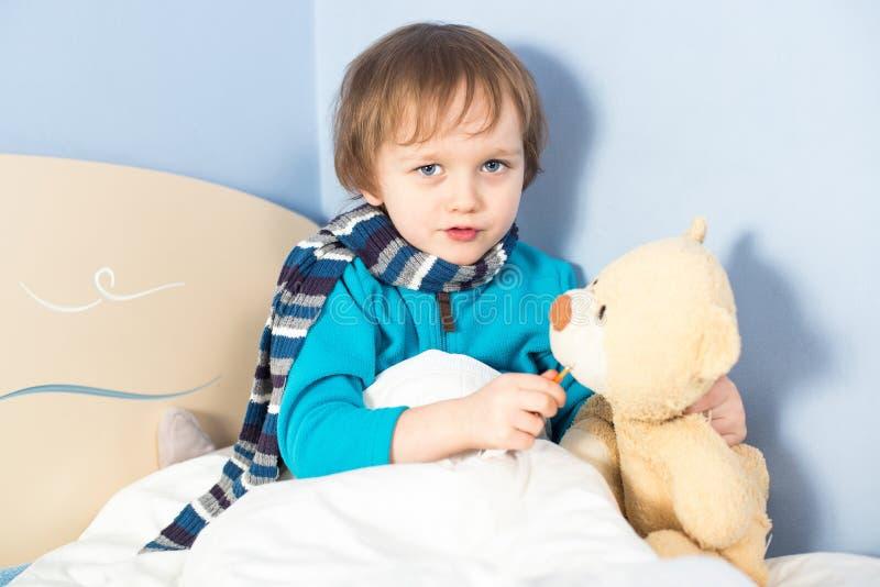 Lite sjukt behandla som ett barn pojken som kontrollerar nallebjörnen, förkroppsligar temperatur royaltyfri fotografi