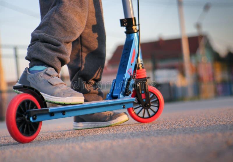 Lite skjuter pojkekörning sparkcykeln - trotinet arkivfoto