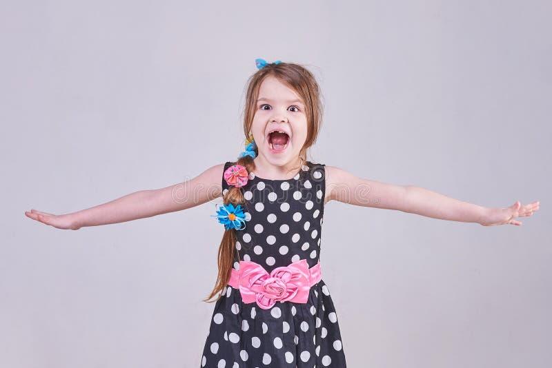 Lite skriker den härliga flickan och att kasta hennes händer i sidorna fotografering för bildbyråer